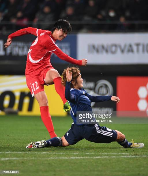 North Korea's forward Kim YunMi shoots to score while Japan's midfielder Mizuho Sakaguchi attempts to block during the women's football match between...