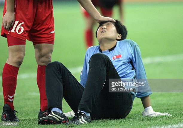 North Korea's goalkeeper Jon Myonghui is consoled by teammate Kong Hyeok after giving up the secong goal against Sweden during their Group B match in...