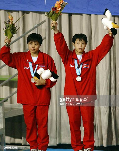 North Korea's Jon HyonJu and Kim KyongJu celebrate after winning the silver medal in the women's synchronized diving finals 09 October 2002 during...