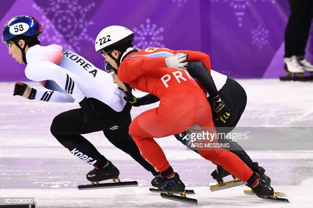 North Korea's Jong Kwang Bom makes contact with Japan's Keita Watanabe in the men's 500m short track speed skating heat event during the Pyeongchang...