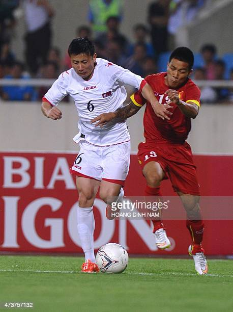 North Korea's Kang Kuk Chol fights for the the ball with Vietnam's Nguyen Quang Hai during a friendly match in Hanoi on May 17 2015 The match ended...