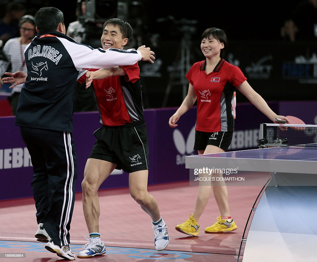 North Korea's Kim Hyok Bong (C) and Kim Jong (L) celebrate with their coach after winning against South Korea's Lee Sangsu and Park Youngsook in the Final match of the mixed doubles of the World Table Tennis Championships on May 18, 2013 in Paris. AFP PHOTO / Jacques DEMARTHON