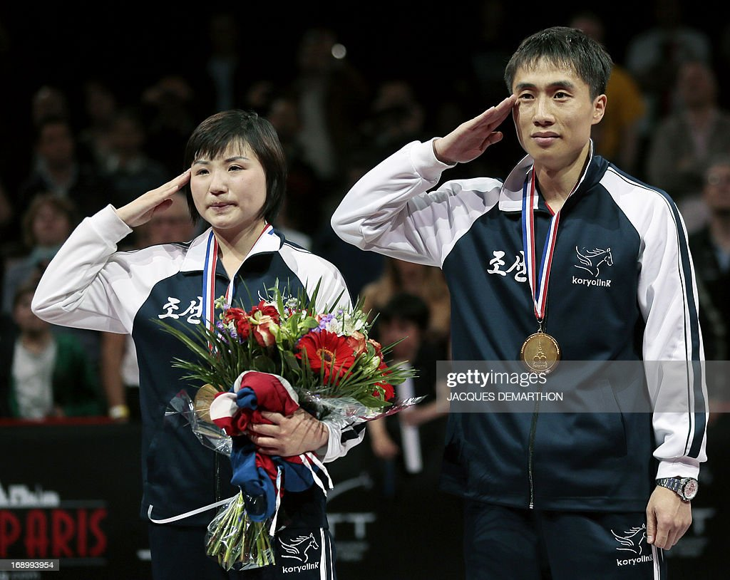 North Korea's Kim Hyok Bong (R) and Kim Jong (L) salute on the podium during their national anthem after winning the mixed doubles title of the World Table Tennis Championships on May 18, 2013 in Paris. AFP PHOTO / Jacques DEMARTHON