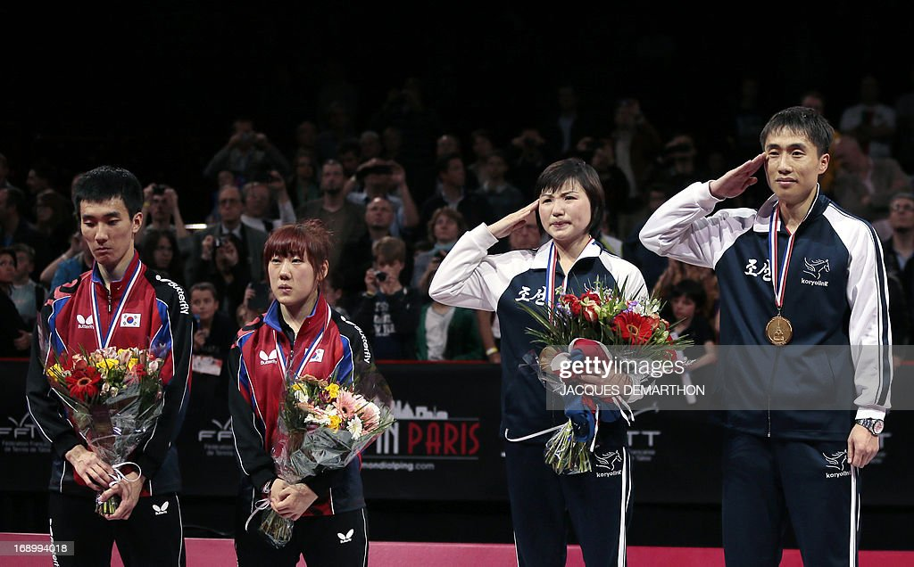 North Korea's Kim Hyok Bong (R) and Kim Jong (2nd R) salute on the podium during their national anthem after winning the mixed doubles title of the World Table Tennis Championships against South Korea's Lee Sangsu (L) and Park Youngsook (2nd L) on May 18, 2013 in Paris. AFP PHOTO / Jacques DEMARTHON