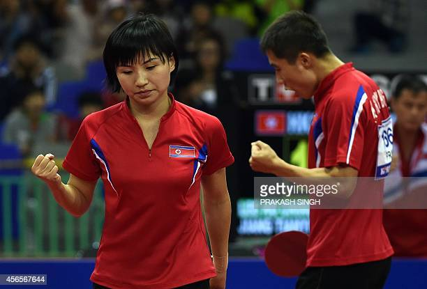 North Korea's Kim Hyokbong and Kim Jong react after a point as they compete against Hong Kong's Jiang Tianyi and Lee Ho Ching during the mixed...
