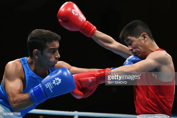 North Korea's Kim Jang Ryong fights with India's Amit in their men's light fly quarterfinal boxing match at the 2018 Asian Games in Jakarta on August...