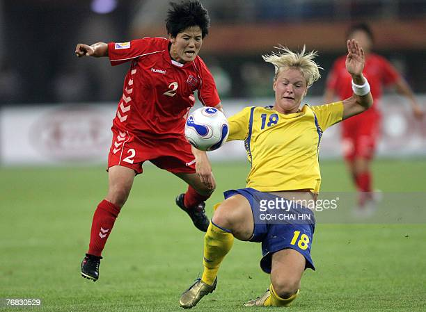 North Korea's Kim Kyonghwa and Sweden's Nilla Fischer tussle for the ball during the Group B match in the 2007 FIFA Women's World Cup football...