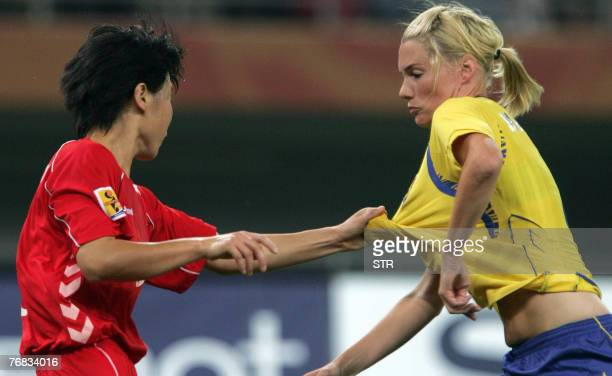 North Korea's Kim Kyonghwa pulls the jersey of Sweden's Hanna Marklund during the Group B match of the 2007 FIFA Women's World Cup football...