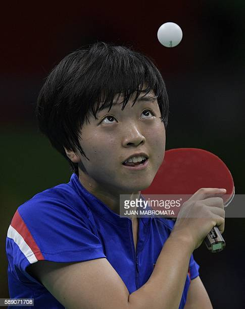 North Korea's Kim Song I eyes the ball as she serves in a women's team quarterfinal table tennis match against China at the Riocentro venue during...