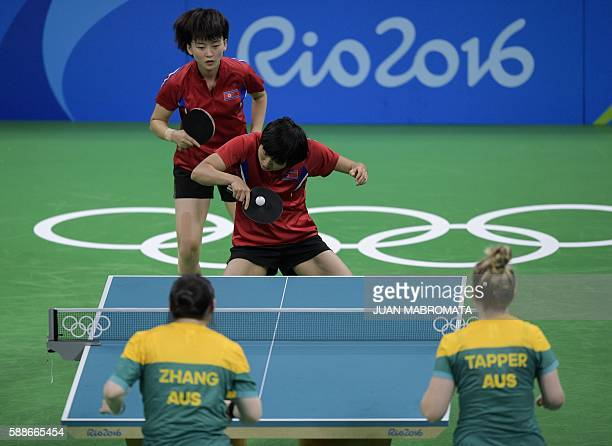 North Korea's Kim Song I hits a shot next to teammate North Korea's Ri Myong Sun in their women's team qualification round table tennis match against...