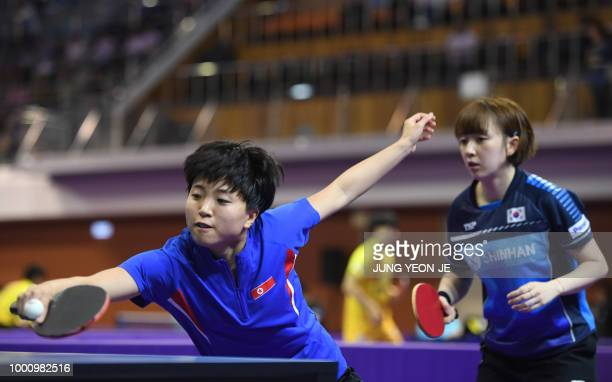 North Korea's Kim Song I returns the ball as teammate South Korea's Suh Hyowon looks on against Uzbekistan's Olga Kim and Regina Kim during the...