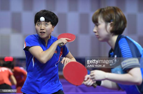 North Korea's Kim Song I serves the ball as teammate South Korea's Suh Hyowon looks on against Uzbekistan's Olga Kim and Regina Kim during the...
