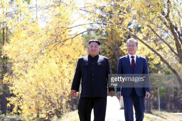 North Korea's leader Kim Jong Un and South Korean President Moon Jaein walk together during a visit to Samjiyon guesthouse on September 20 2018 in...