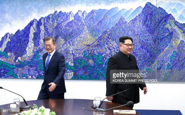 North Korea's leader Kim Jong Un and South Korea's President Moon Jaein walk back to their seats after a photo session during their summit in the...