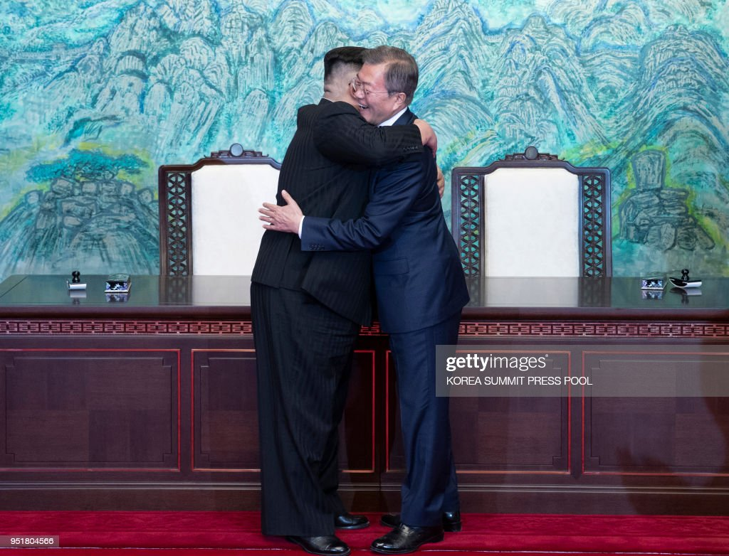 TOPSHOT - North Korea's leader Kim Jong Un (L) and South Korea's President Moon Jae-in (R) hug during a signing ceremony near the end of their historic summit at the truce village of Panmunjom on April 27, 2018. - The leaders of South and North Korea embraced warmly after signing a statement in which they declared 'there will be no more war on the Korean Peninsula'.