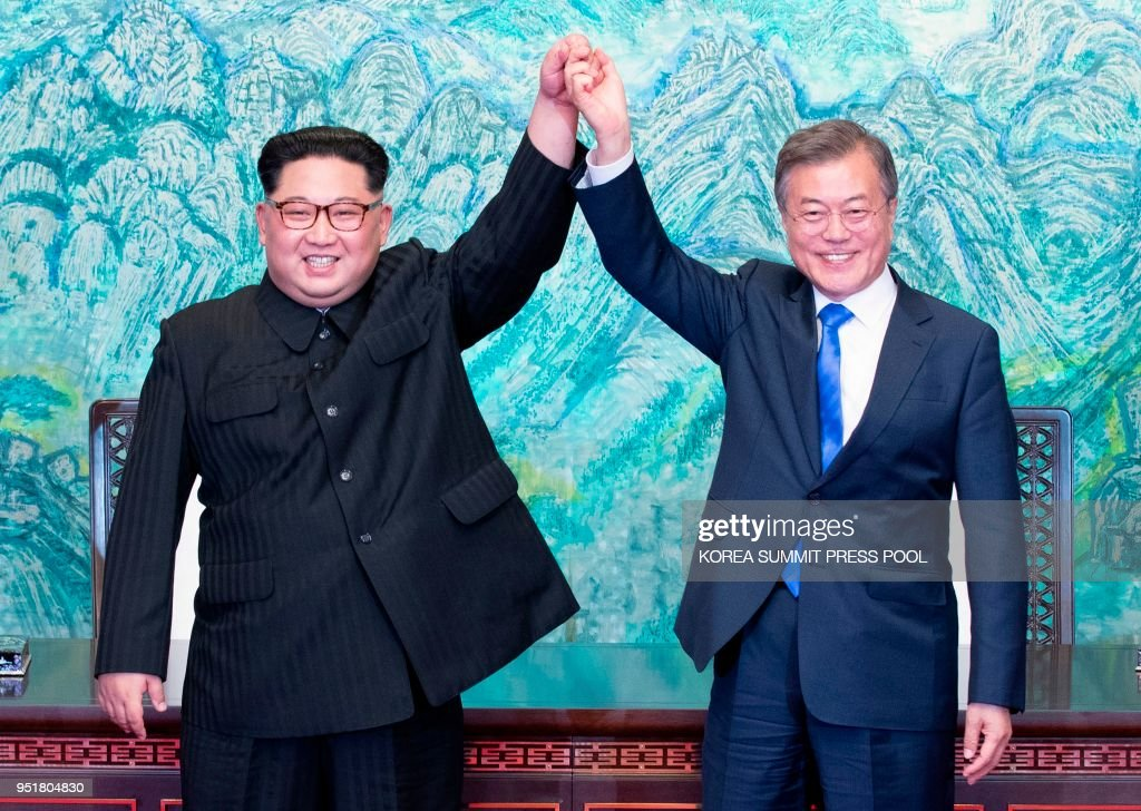 TOPSHOT - North Korea's leader Kim Jong Un (L) and South Korea's President Moon Jae-in (R) raise their jointed hands during a signing ceremony near the end of their historic summit at the truce village of Panmunjom on April 27, 2018. - The leaders of South and North Korea embraced warmly after signing a statement in which they declared 'there will be no more war on the Korean Peninsula'.