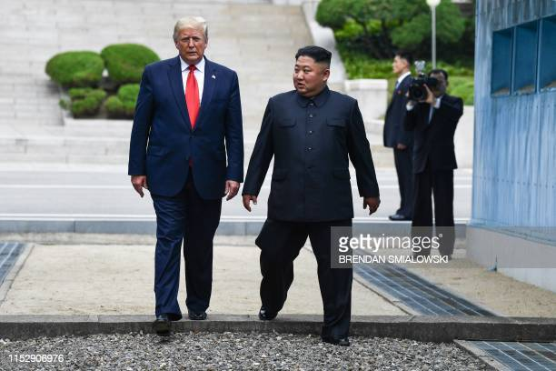 TOPSHOT North Korea's leader Kim Jong Un and US President Donald Trump cross south of the Military Demarcation Line that divides North and South...