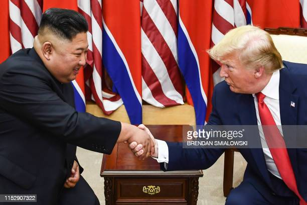 TOPSHOT North Korea's leader Kim Jong Un and US President Donald Trump shake hands during a meeting on the south side of the Military Demarcation...