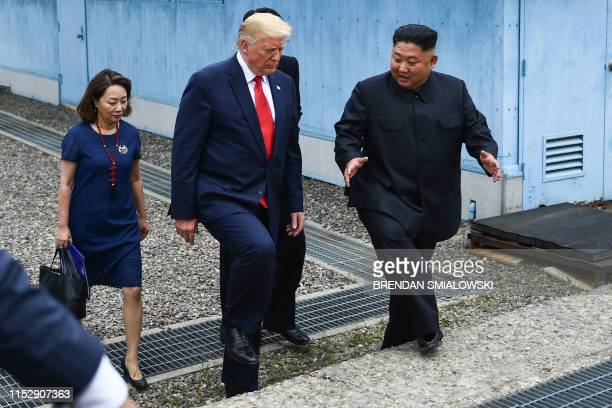 North Korea's leader Kim Jong Un and US President Donald Trump walk together south of the Military Demarcation Line that divides North and South...