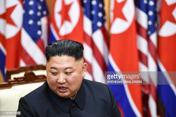 North Korea's leader Kim Jong Un attends a meeting with US President Donald Trump on the south side of the Military Demarcation Line that divides...