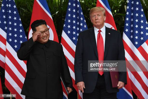 North Korea's leader Kim Jong Un poses with US President Donald Trump after taking part in a signing ceremony at the end of their historic USNorth...