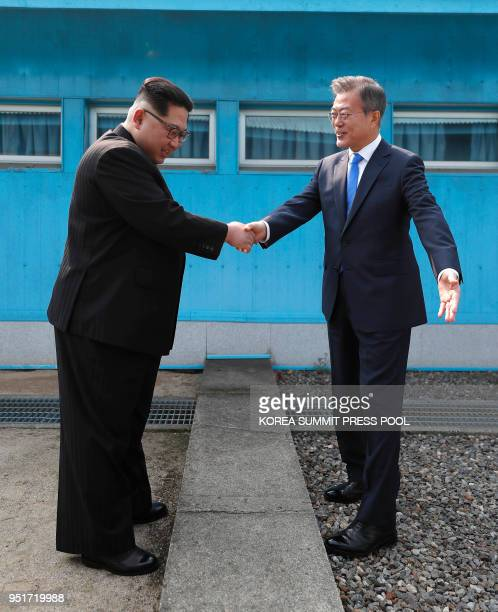 North Korea's leader Kim Jong Un shakes hands with South Korea's President Moon Jaein at the Military Demarcation Line that divides their countries...