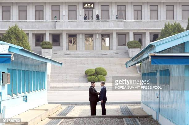 TOPSHOT North Korea's leader Kim Jong Un shakes hands with South Korea's President Moon Jaein at the Military Demarcation Line that divides their...