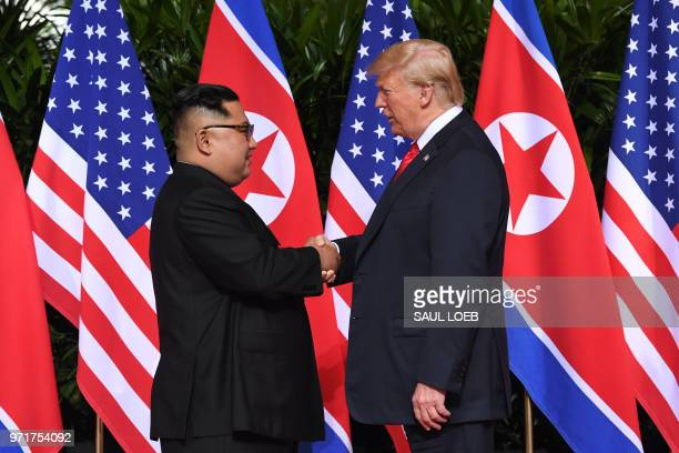 TOPSHOT North Korea's leader Kim Jong Un shakes hands with US President Donald Trump at the start of their historic USNorth Korea summit at the...