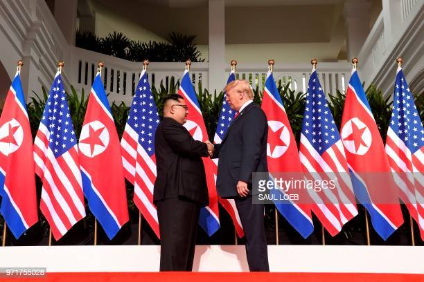 North Korea's leader Kim Jong Un shakes hands with US President Donald Trump at the start of their historic USNorth Korea summit at the Capella Hotel...