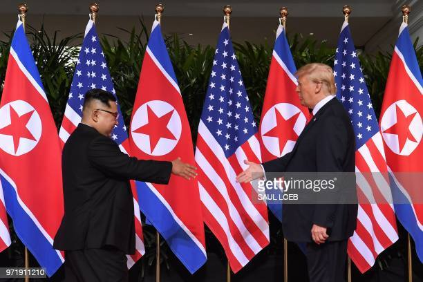 North Korea's leader Kim Jong Un shakes hands with US President Donald Trump at the start of their historic US-North Korea summit, at the Capella...