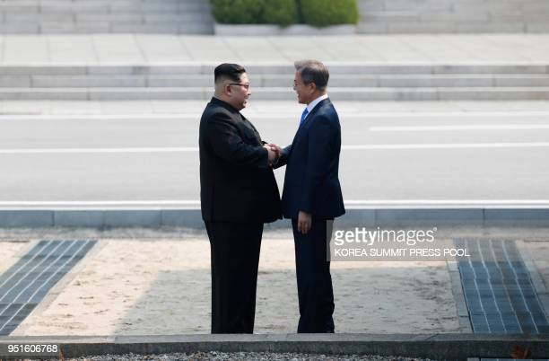 North Korea's leader Kim Jong Un shakes with South Korea's President Moon Jae-in at the Military Demarcation Line that divides their countries ahead...