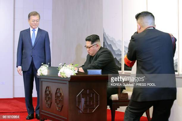 North Korea's leader Kim Jong Un signs the guest book next to South Korea's President Moon Jaein during the InterKorean summit at the Peace House...