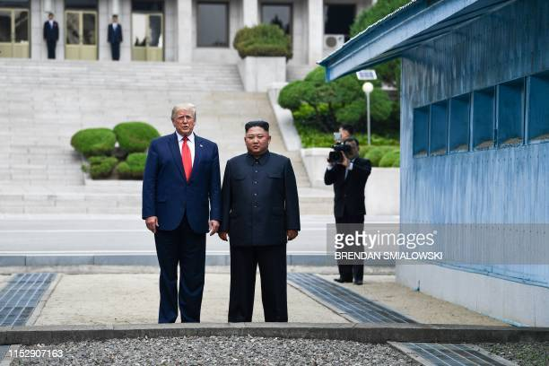 North Korea's leader Kim Jong Un stands with US President Donald Trump north of the Military Demarcation Line that divides North and South Korea in...