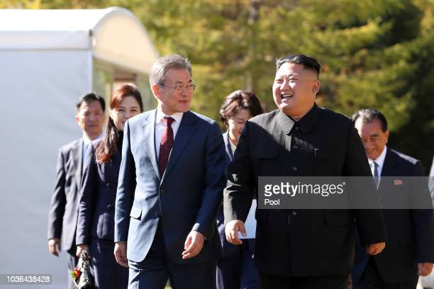 North Korea's leader Kim Jong Un walk with South Korean President Moon Jae-in during a visit to Samjiyon guesthouse in Samjiyon on September 20, 2018...
