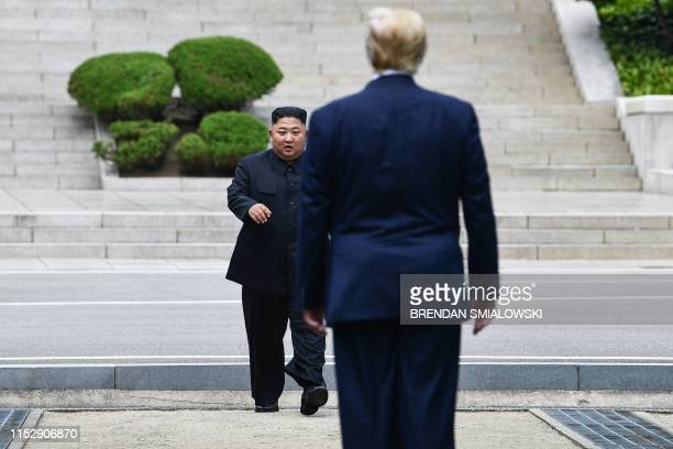 TOPSHOT North Korea's leader Kim Jong Un walks to greet US President Donald Trump at the Military Demarcation Line that divides North and South Korea...