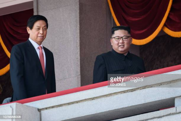 North Korea's leader Kim Jong Un walks with China's Chairman of the Standing Committee of the National People's Congress Li Zhanshu on a balcony of...
