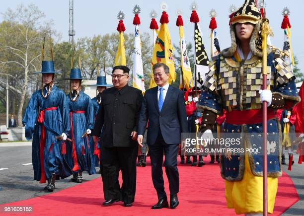 North Korea's leader Kim Jong Un walks with South Korea's President Moon Jae-in after meeting at the Military Demarcation Line that divides their...