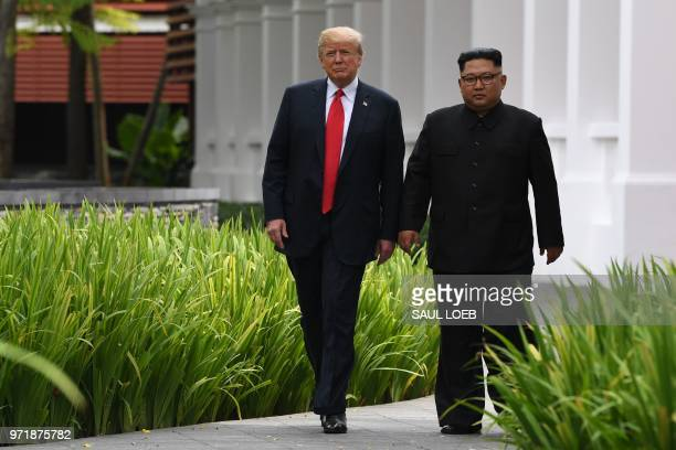 TOPSHOT North Korea's leader Kim Jong Un walks with US President Donald Trump during a break in talks at their historic USNorth Korea summit at the...