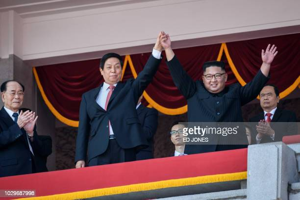 North Korea's leader Kim Jong Un waves with China's Chairman of the Standing Committee of the National People's Congress Li Zhanshu from a balcony of...