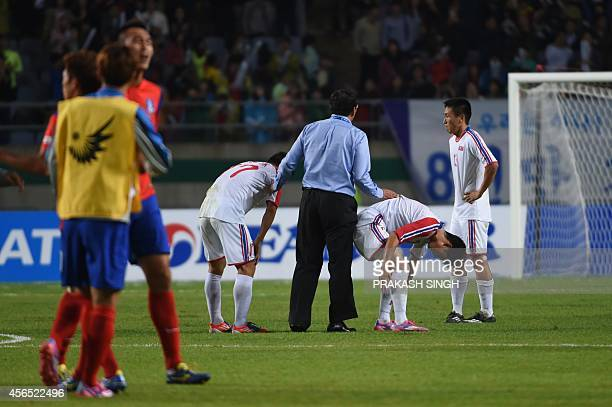 North Korea's players are comforted by an official after their defeat in the men's football gold medal match of the 17th Asian Games between South...
