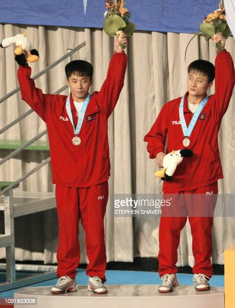 North Korea's Ri JongNam and Jo ChoiRyong celebrate after receiving the silver in the men's 10m Synchronized Diving event 08 October 2002 at the 14th...