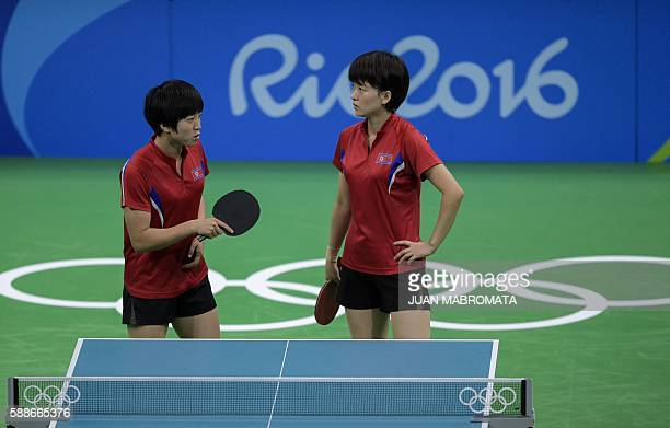 North Korea's Ri Myong Sun and North Korea's Kim Song I look on during the women's team qualification round table tennis match against Australia at...