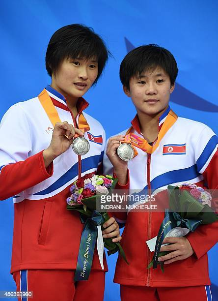 North Korea's silver medalists Kim Ungyong and Song Namhyang pose with their medals after the women's synchronised 10m platform diving during the...