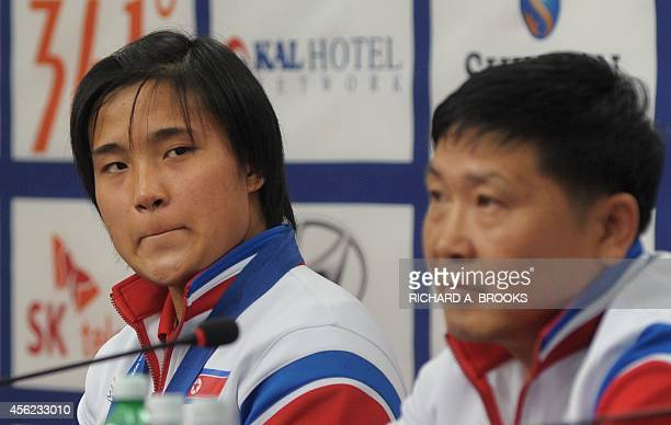 North Korea's weightlifter Kim UnJu glaces over at her coach Choe NongGyun during a press conference at the main media centre for the 17th Asian...