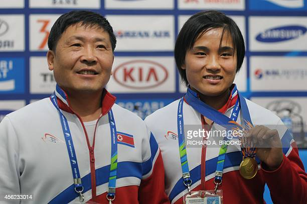 North Korea's weightlifter Kim UnJu poses with her coach Choe NongGyun after a press conference at the main media centre for the 17th Asian Games in...
