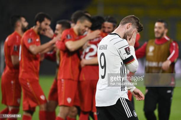 North Macedonia players celebrate as Germany's forward Timo Werner walks past after the FIFA World Cup Qatar 2022 qualification football match...