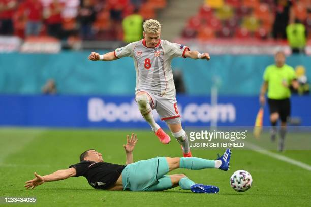 North Macedonia's defender Ezgjan Alioski jumps over Austria's defender Stefan Lainer during the UEFA EURO 2020 Group C football match between...