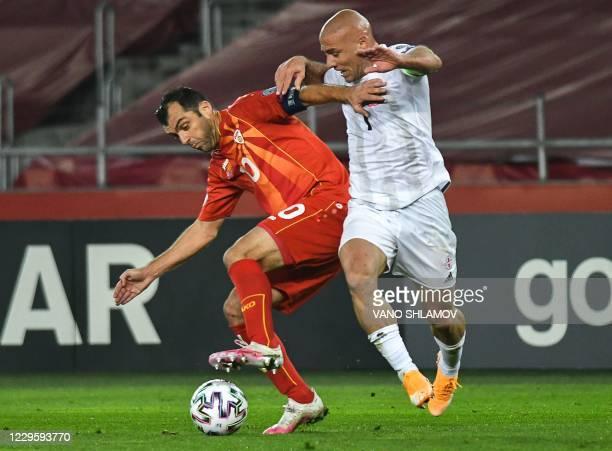North Macedonia's forward Goran Pandev is challenged by Georgia's midfielder Jaba Kankava during the UEFA European qualifiers play-off final football...