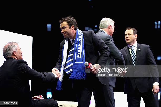 North Melbourne Coach Brad Scott shakes hands after speaking during the 2013 Blackwoods North Melbourne Grand Final Breakfast at Etihad Stadium on...