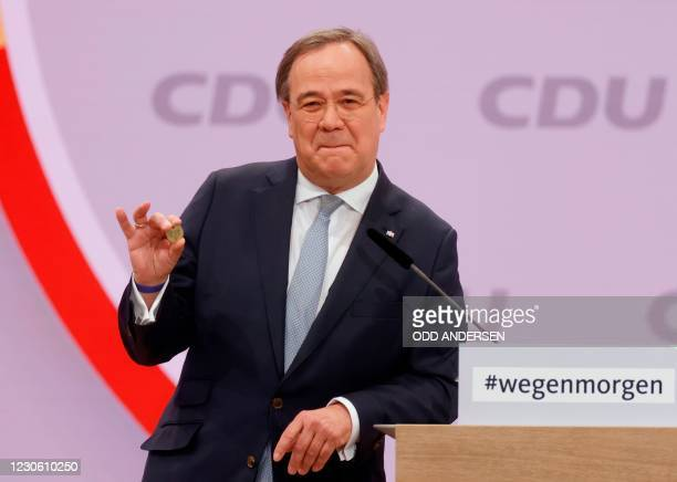 North Rhine-Westphalia's State Premier and candidate as leader of the Christian Democratic Union Armin Laschet shows a luck coin offered to him by...